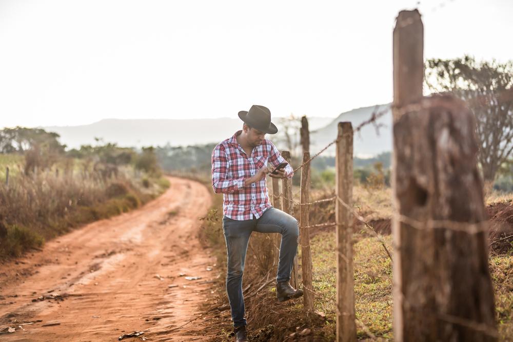 Homem mexendo no celular apoiado na cerca de arame farpado