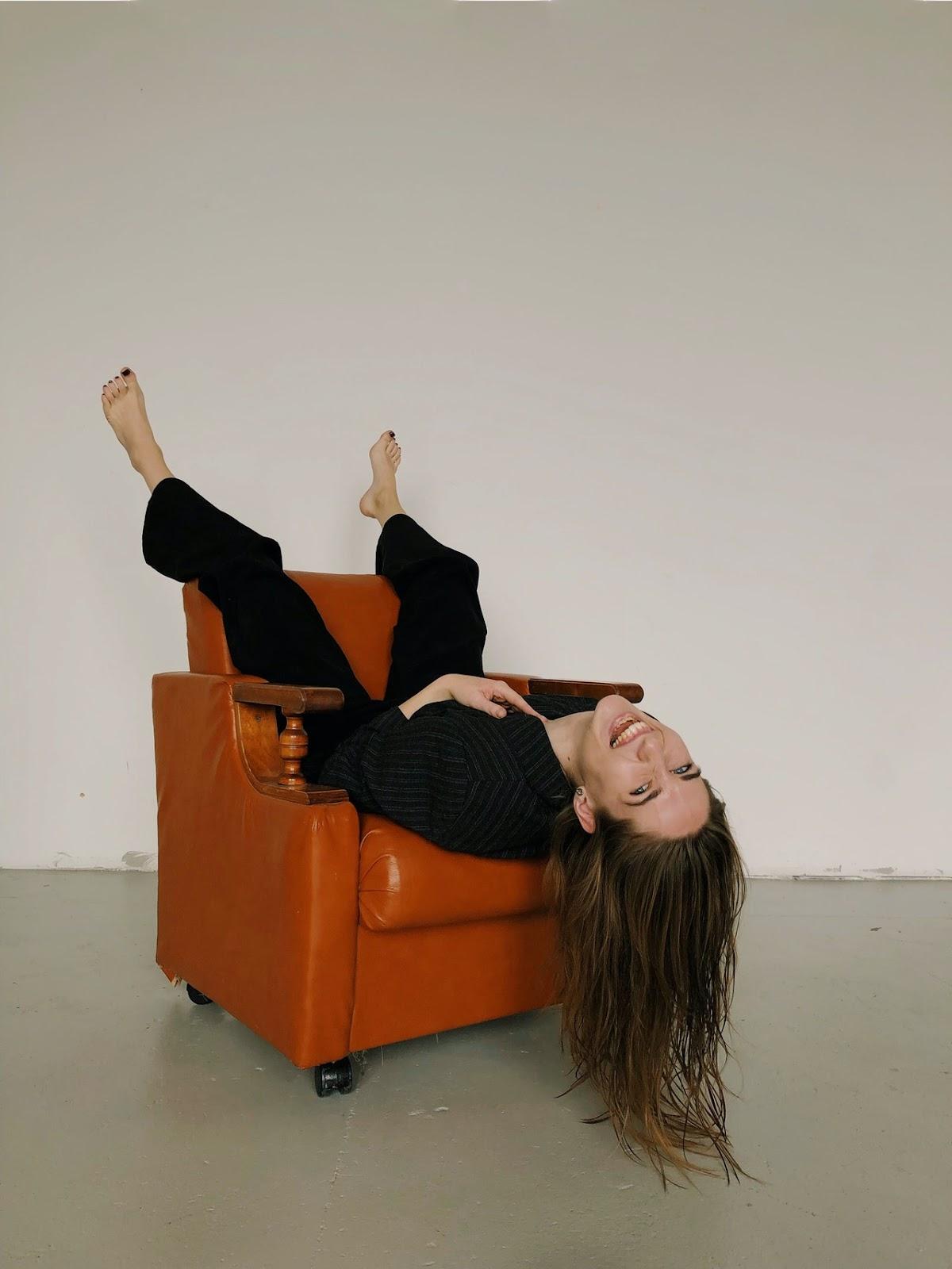 Frau lacht auf Sessel
