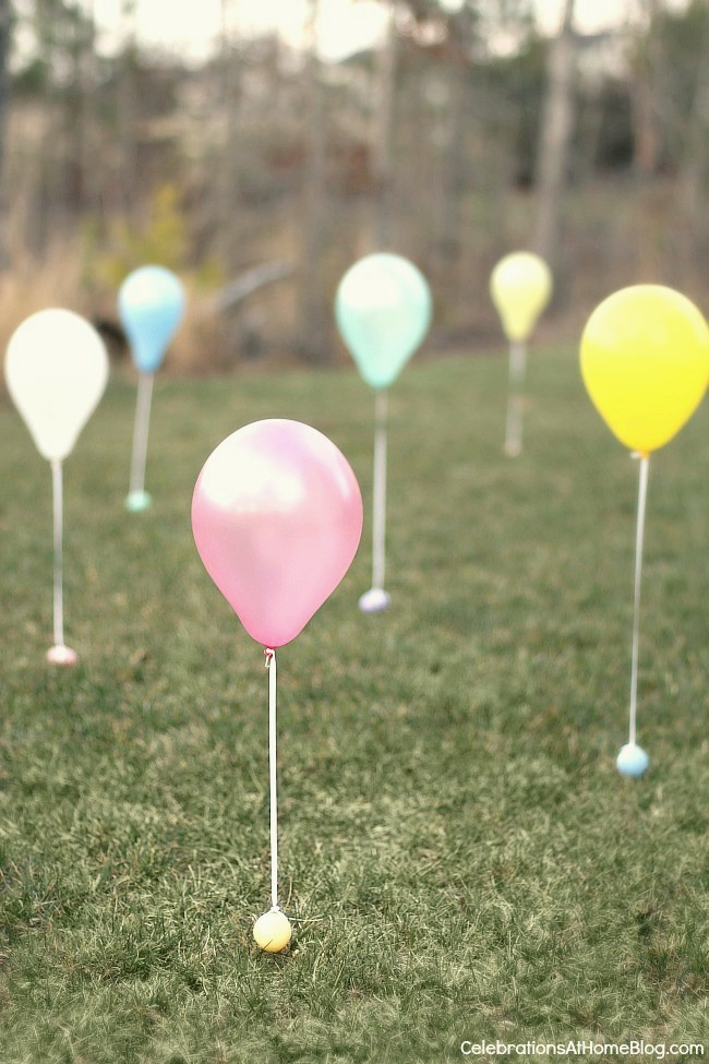 Six balloons tied to plastic Easter Eggs spread out across a field.