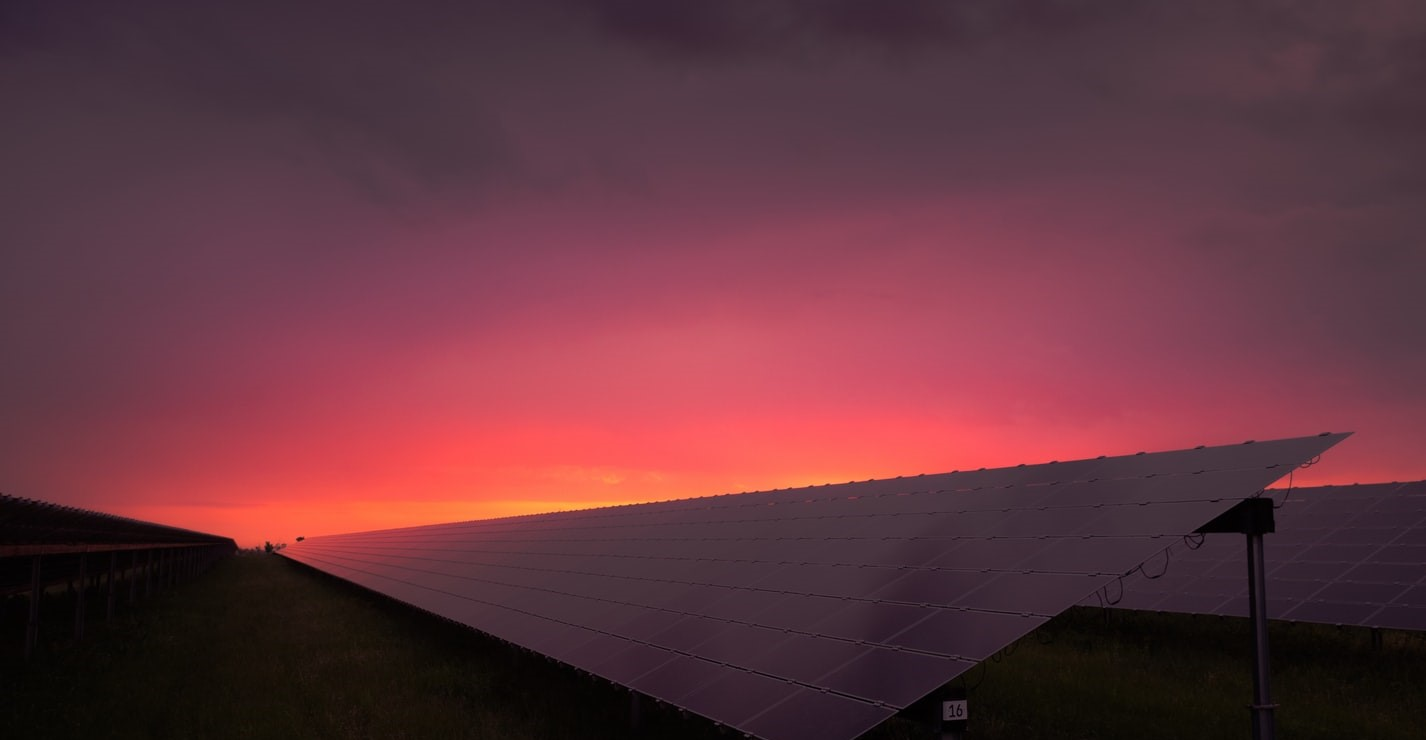 This is a beautiful sunset behind a solar panel, showing that renewable energy sources don't have to be an eyesore