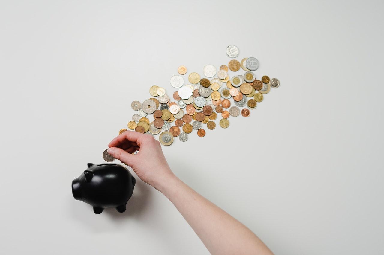 Een spaarvarken met geld rond op een witte achtergrond