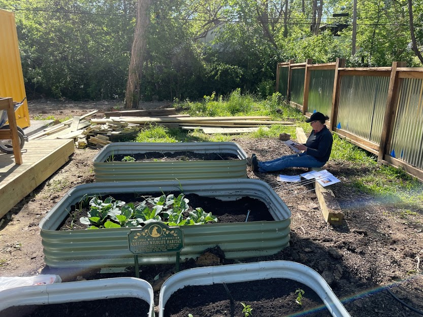 A volunteer sits near raised garden beds