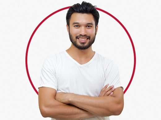 Smiling young man standing confidently and wearing grey T-shirt, happy after Canesten jock itch treatment