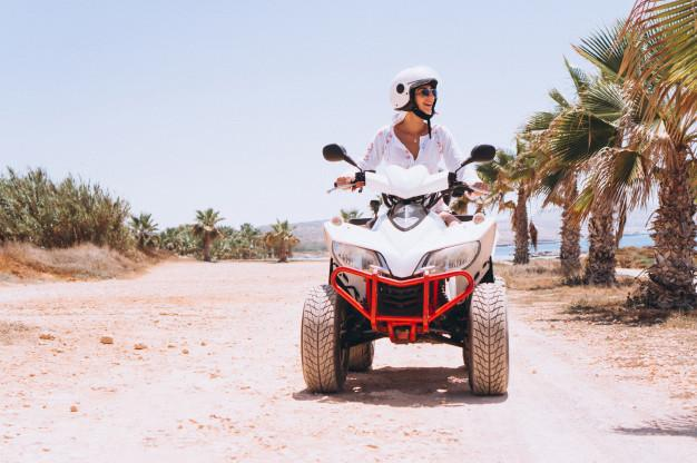 Woman travelling on quad by th ocean Free Photo