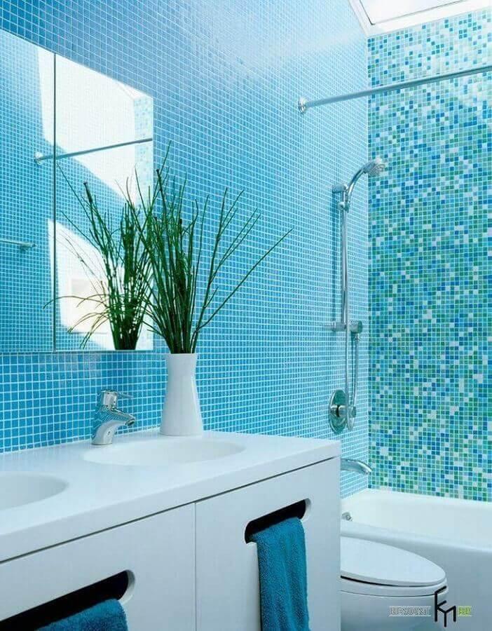 Banheiro todo revestido com pastilhas azul com banheira e louças brancas