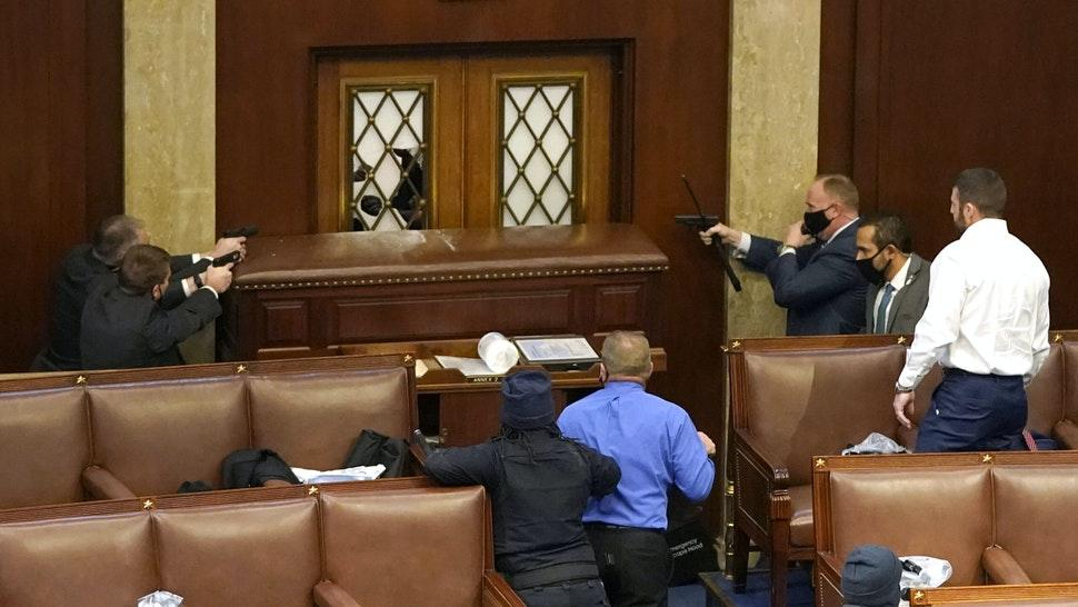 WASHINGTON, DC - JANUARY 06: U.S. Capitol police officers point their guns at a door that was vandalized in the House Chamber during a joint session of Congress on January 06, 2021 in Washington, DC. Congress held a joint session today to ratify President-elect Joe Biden's 306-232 Electoral College win over President Donald Trump. A group of Republican senators said they would reject the Electoral College votes of several states unless Congress appointed a commission to audit the election results.