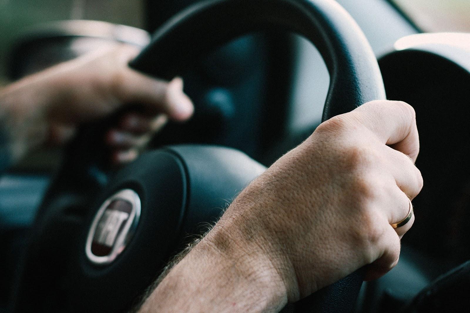 Duas mãos segurando o volante do carro.