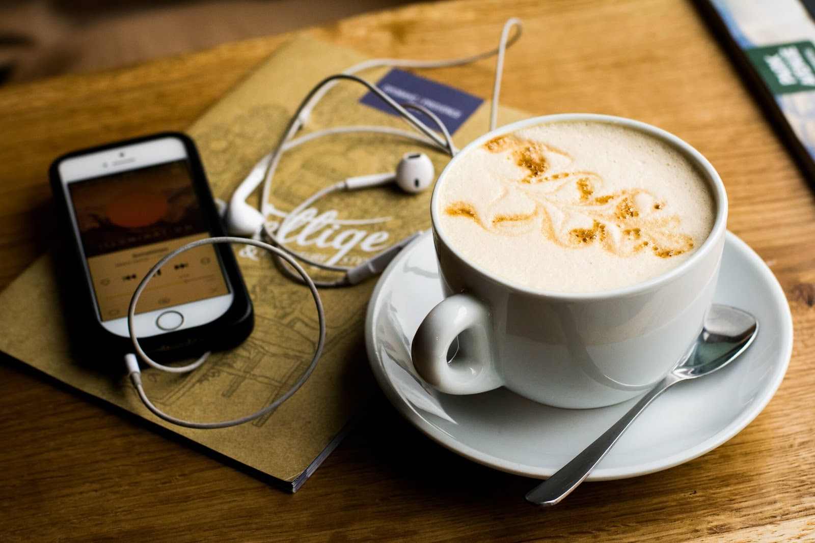A phone with headphones, playing music on a coffee shop table
