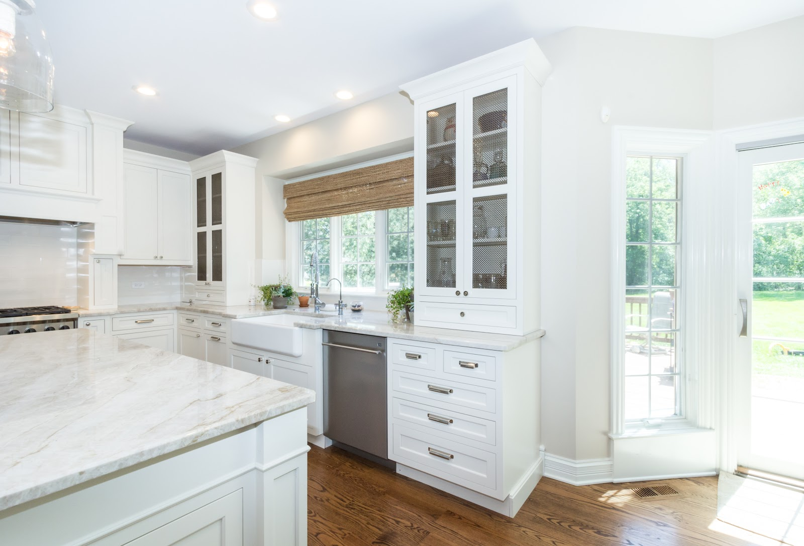 White kitchen with upper glass door panel cabinets flanking either side of the window above a white porcelain sink. Featuring stainless steel appliances and a nickel faucet.
