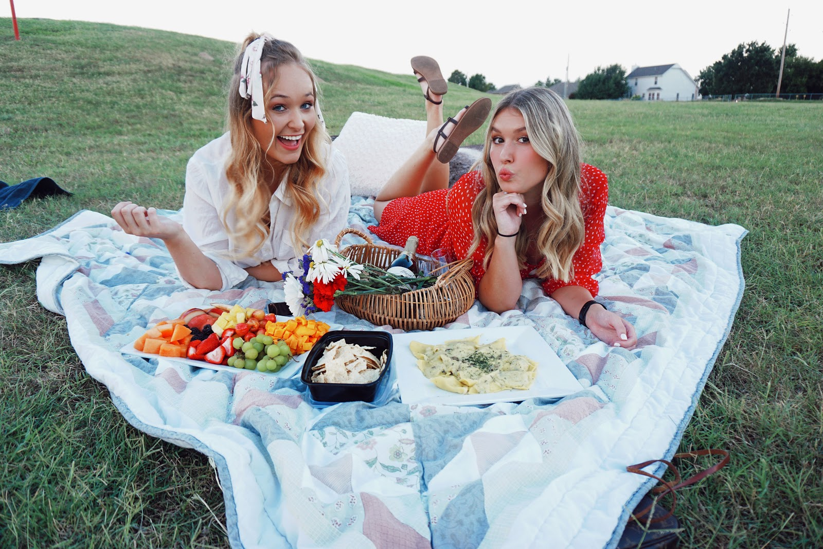 outdoor picnic with wine, fruit, summer food, and flowers