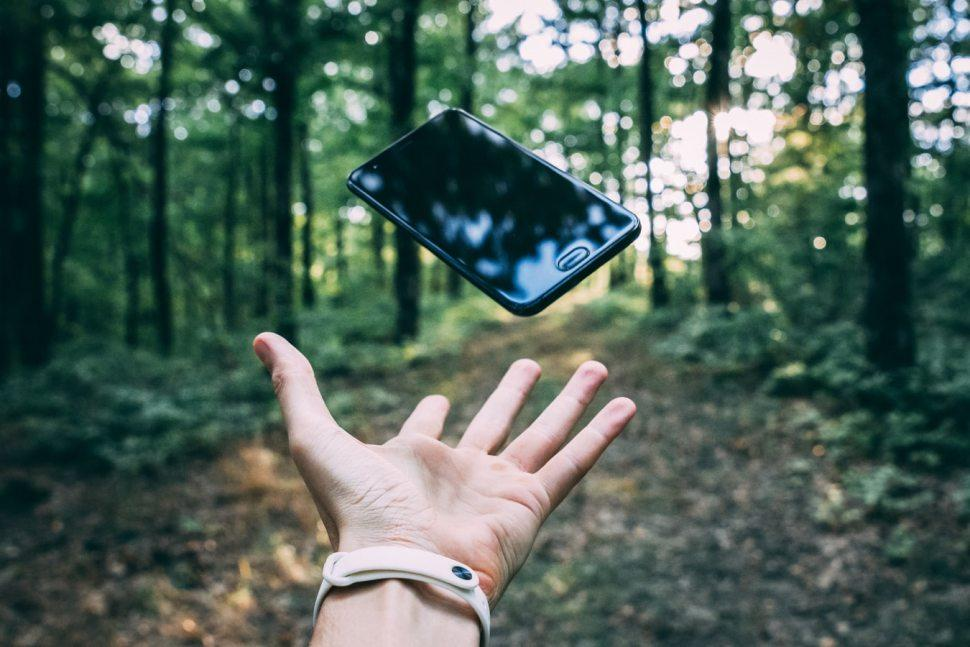 Phone being tossed in the air in woods