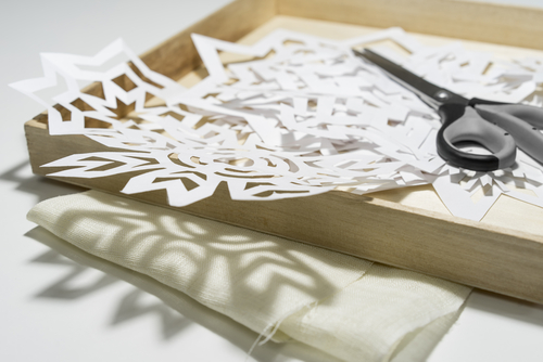 A cut out paper snowflakes on a table with a pair of scissors next to it suitable for decorating an apartment.