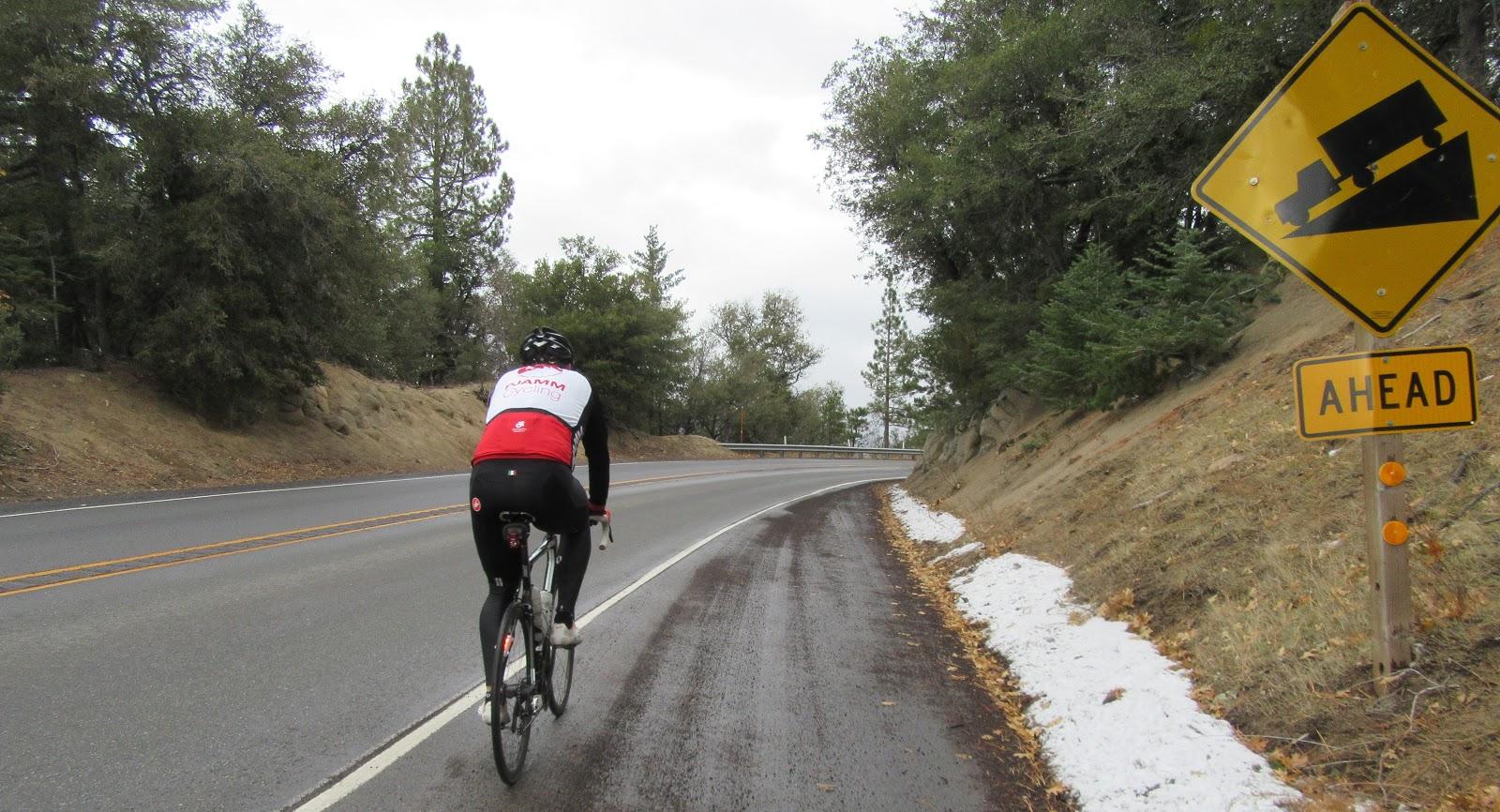 Climbing Onyx Summit by bike - cyclist on bike with steep grade sign.