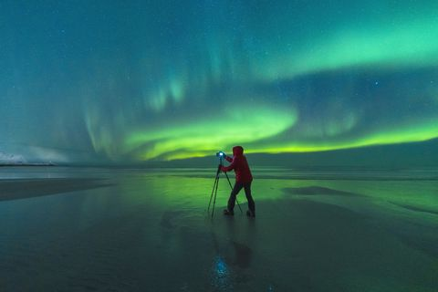 Photographer on Skagsanden beach during Northern Lights, Norway