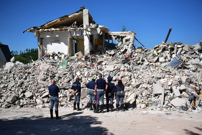 Police officers view the remains of a building that was destroyed during an earthquake, on August 25, 2016 in Amatrice, Italy. Credit: Carl Court / Getty Images.