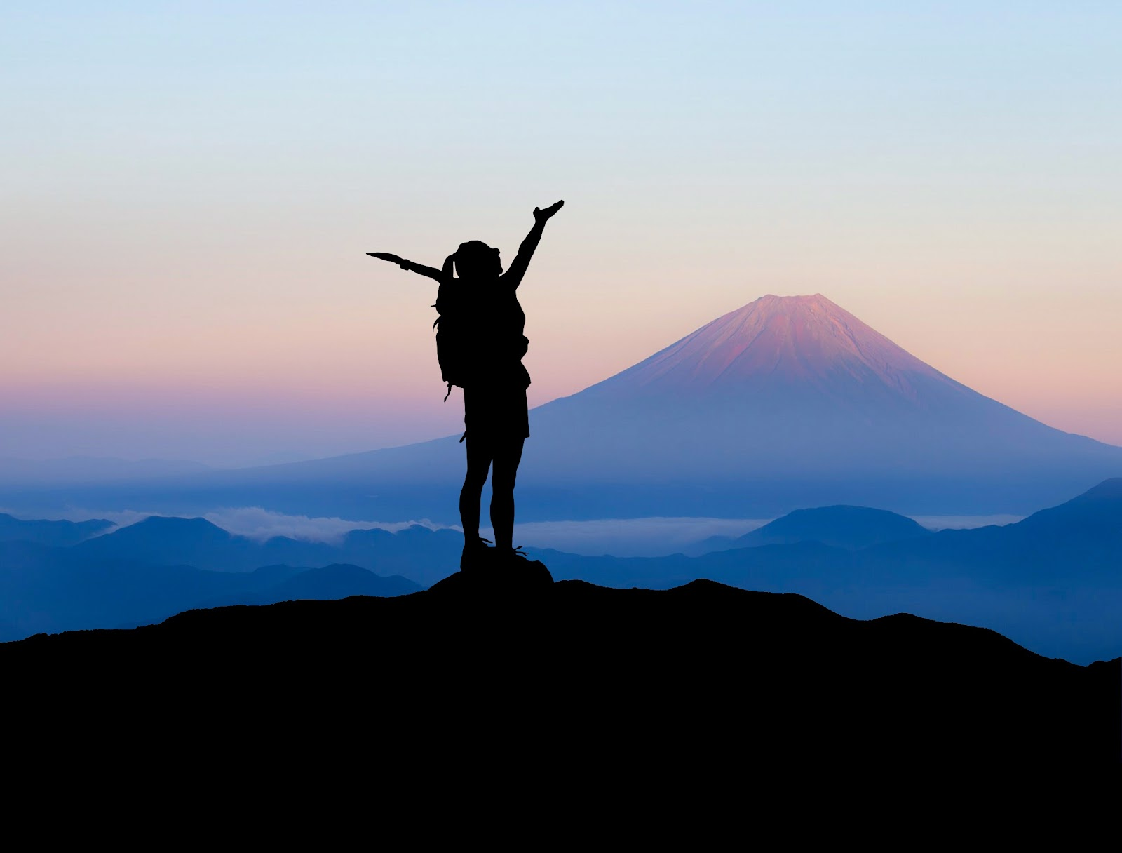 Silhouette of mountain climber at the top of a peak with the sun shining through a purple peak further in the distance. They're celebrating their success.