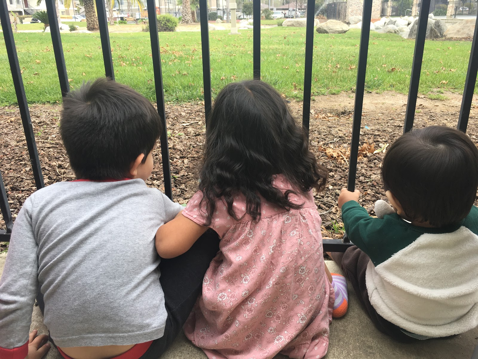 A creative activity you can do with kids is to have a play date. 3 kids sitting outside looking out