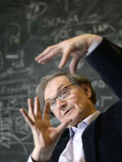 Sir Roger Penrose from the mid-torso & up gesticulating in front of a filled chalkboard.