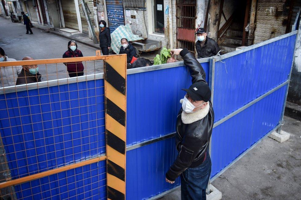 Um homem entrega comida em um bairro isolado na cidade chinesa de Wuhan, epicentro do surto, em 23 de fevereiro.