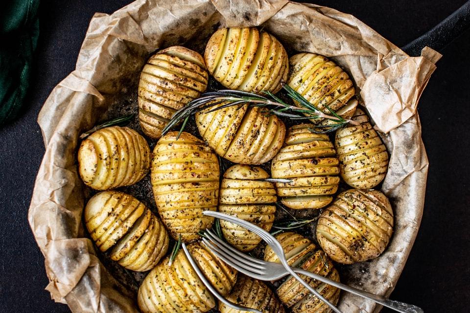 Batatas em rodelas finas, com aparência dourada e bem assada. Para aromatizar e decorar, há ramos de alecrim inteiros entre as batatas.