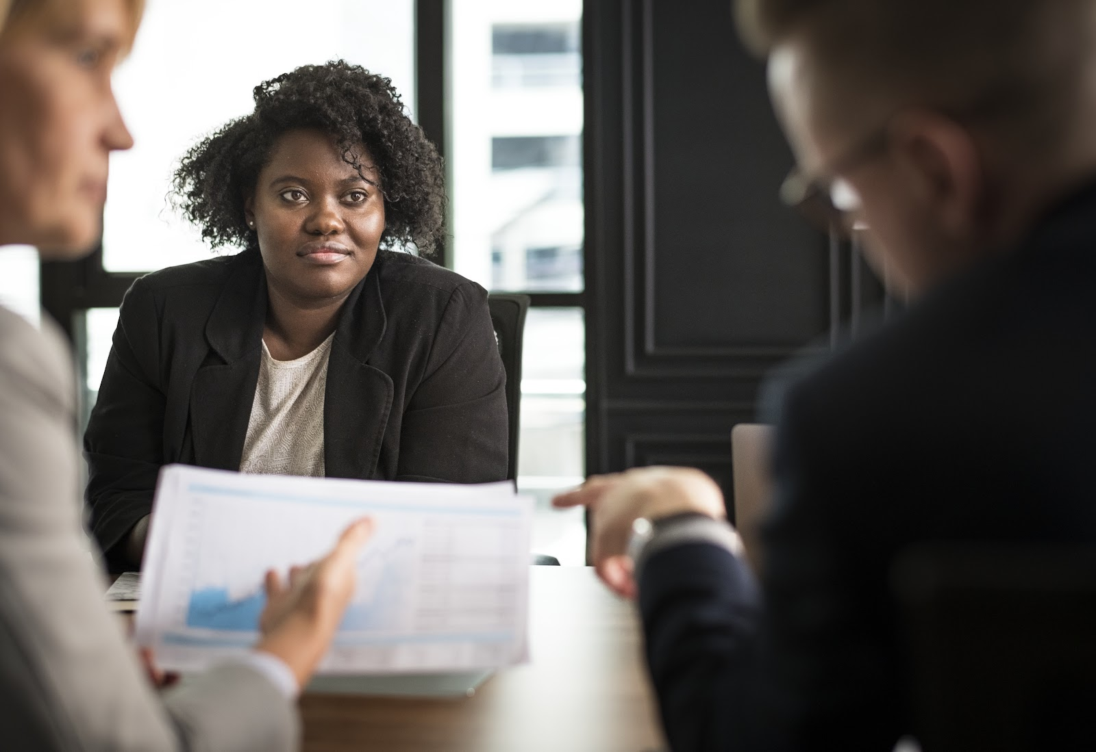 Uma mulher ouvindo dois homens conversar sobre um gráfico