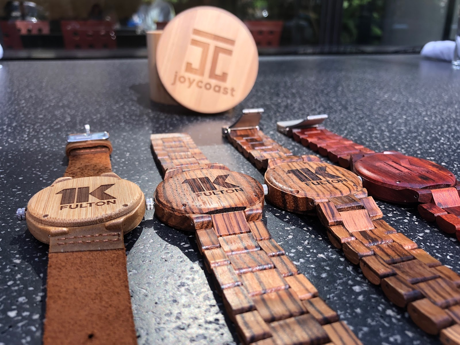 Various styles of wooden watches engraved with corporate name and logo. Note wooden piece engraved with Joycoast name and logo in background.