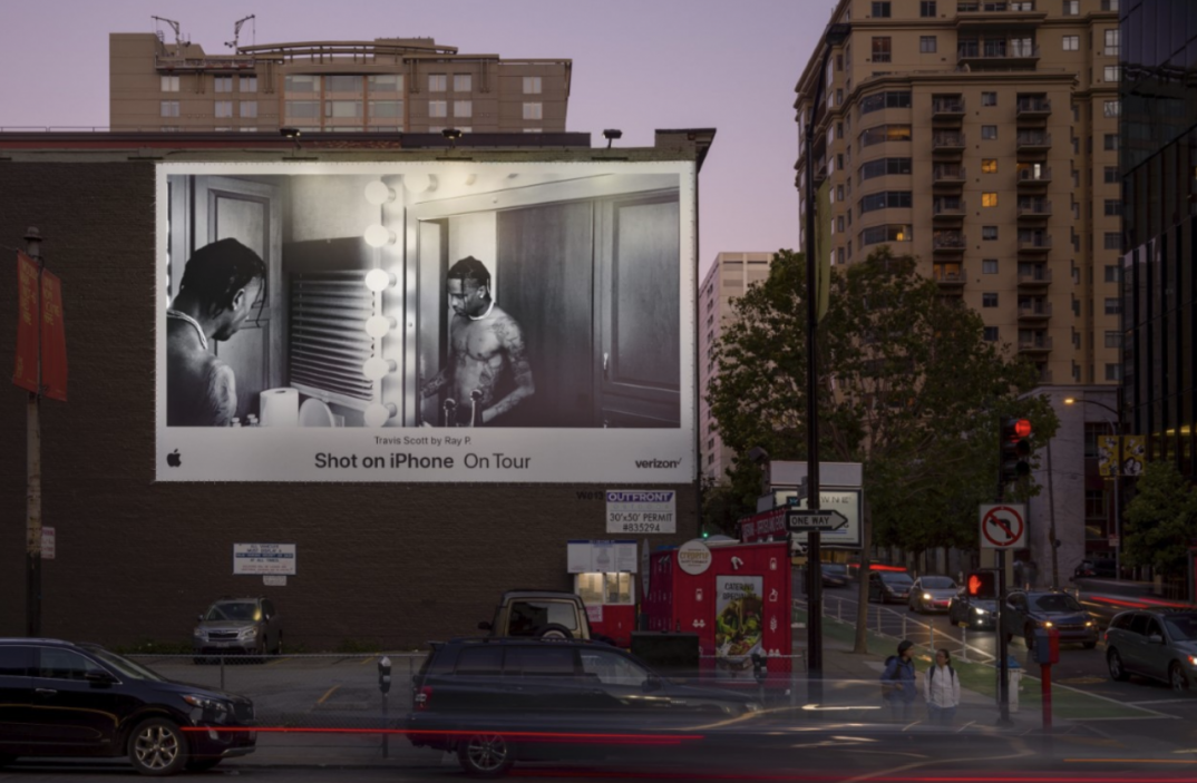 A 'Shot on iPhone' billboard with a black and white image of an artist looking in the mirror.