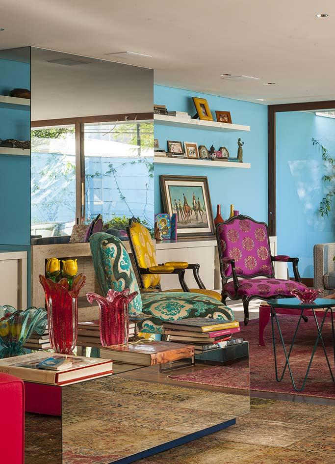 Ambiente com parede azul, espelho e poltronas coloridas.