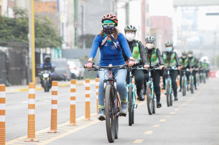 Ciclista e companhia policial dedicada ao ciclismo em fila com máscara e capacete