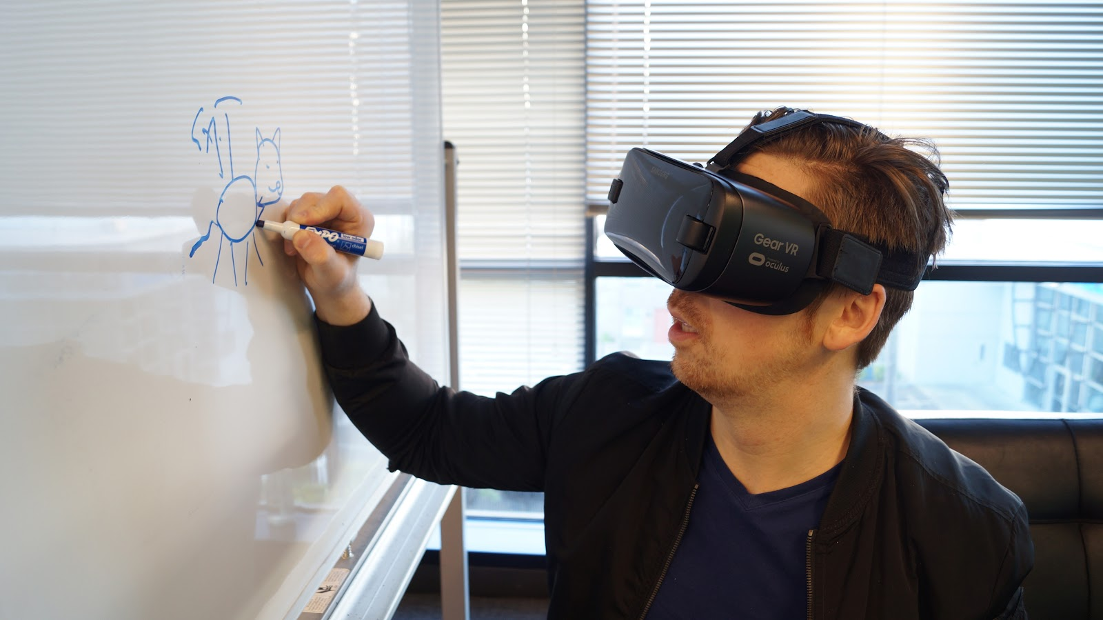 A person wearing VR goggles while drawing on a white board