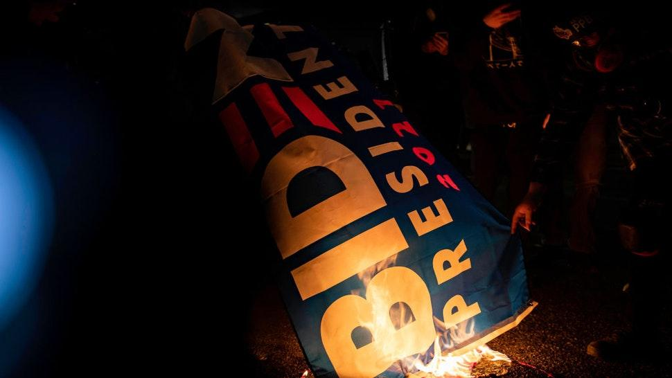 PORTLAND, OR, UNITED STATES - JANUARY 20: Protesters burn a Biden for President flag outside of the Federal Immigration and Customs Enforcement [ICE] building in Portland, Oregon on January 20, 2021. (Photo by Maranie R. Staab for The Washington Post via Getty Images)
