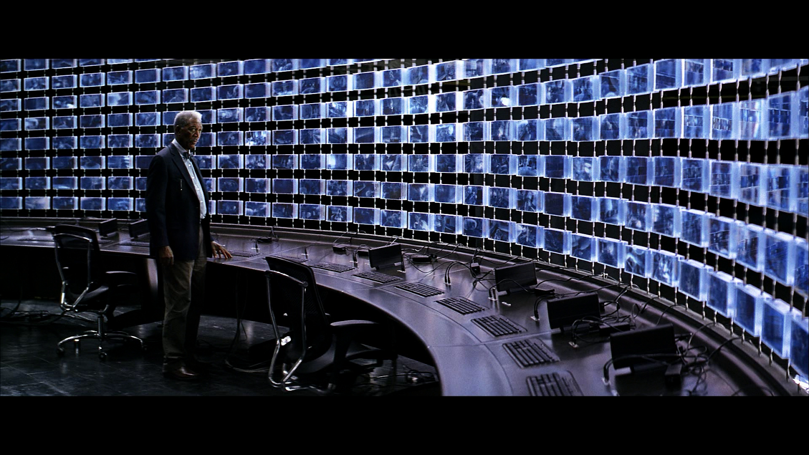 Lucius Fox staring at hundreds of screens that make up a single image