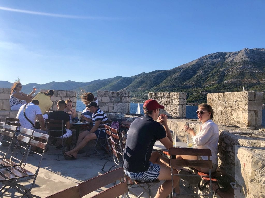 People sitting outside in Massimo Bar on Korcula, sitting at distanced tables in what looks like the top of a castle, overlooking the mountains on shore.