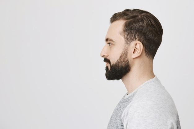 Profile of stylish bearded man made new hairstyle at barber shop  faded beard