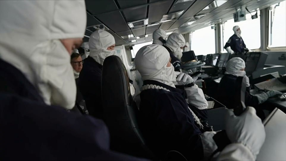 Members of the ship's crew were pictured wearing anti-flash gear, which protects them fromflame exposure and heat