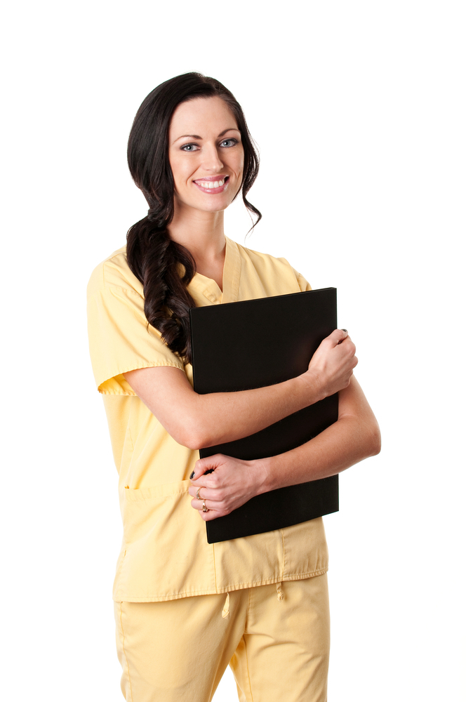 Nurse smiling and standing while wearing yellow uniform.