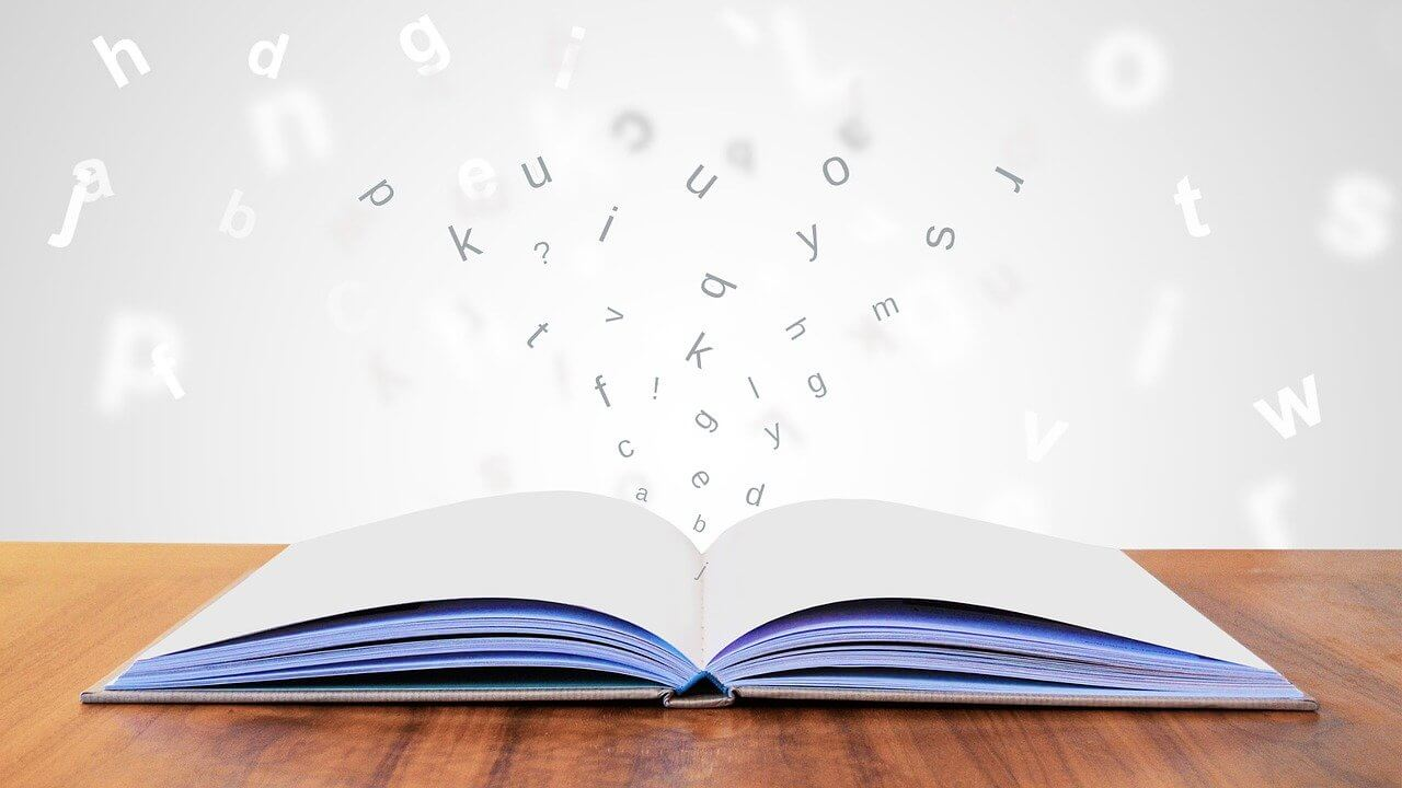 開いた本からアルファベットが飛び出てきている