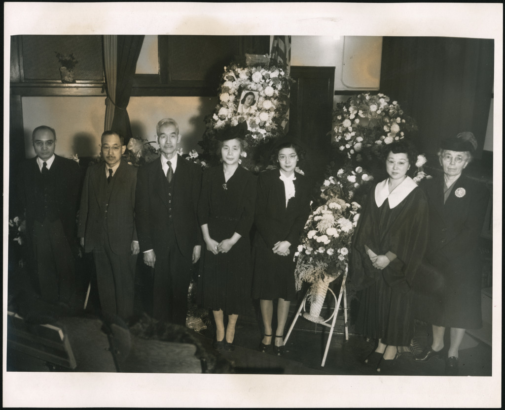 A group of men and women at the funeral of a Japanese American girl killed in the atomic bombing of Hiroshima. There are flower wreaths and a photo of the girl in the background.