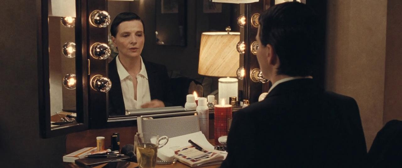 Juliette Binoche as Maria playing Helena in 'Clouds of Sils Maria' (2014). Maria is in character as Helena, sitting at her dressing table in the theatre, looking at her reflection in the mirror.