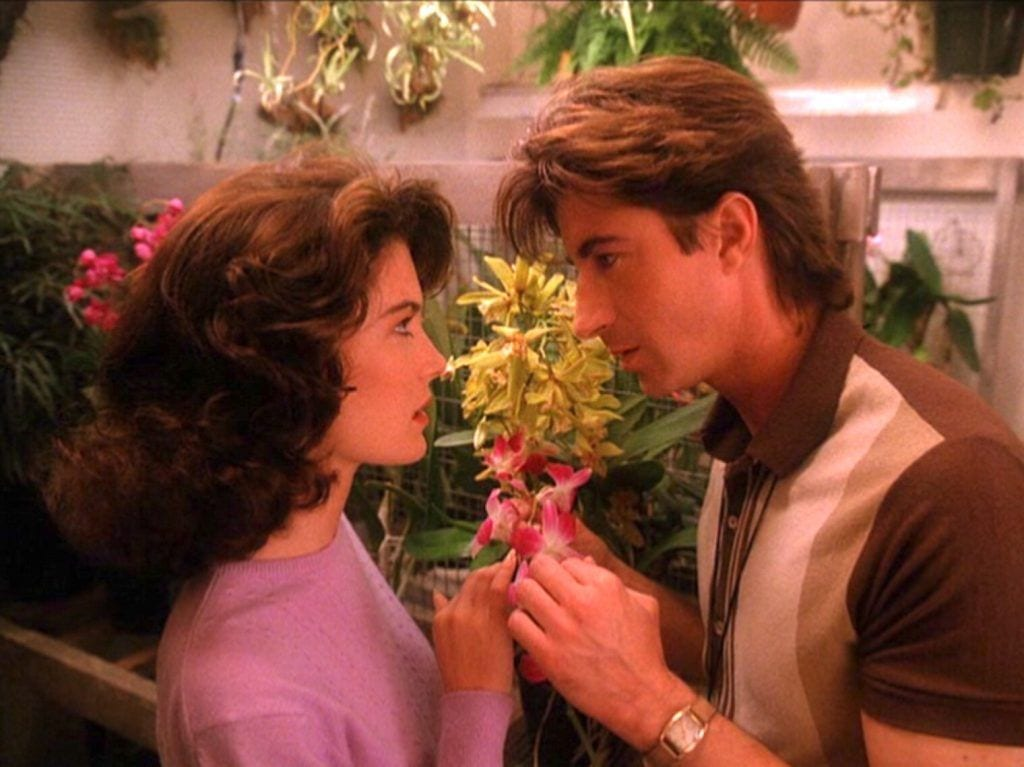 donna and harold hold a pink orchid and share an intense moment in his gardening shed
