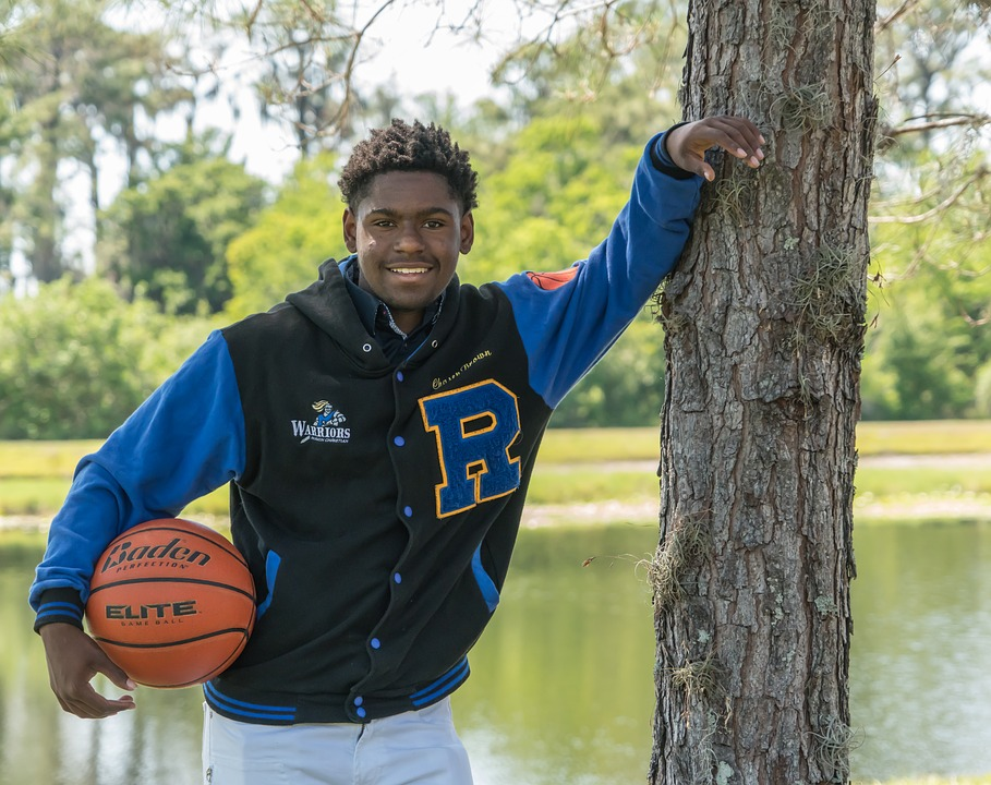 high school senior holding basketball and leaning against tree