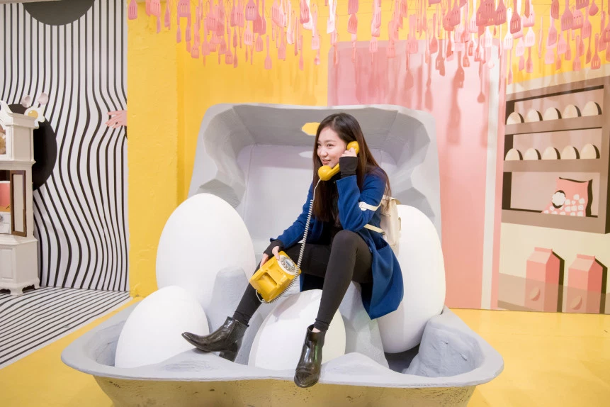 Image of person holding a phone and sitting on giant eggs