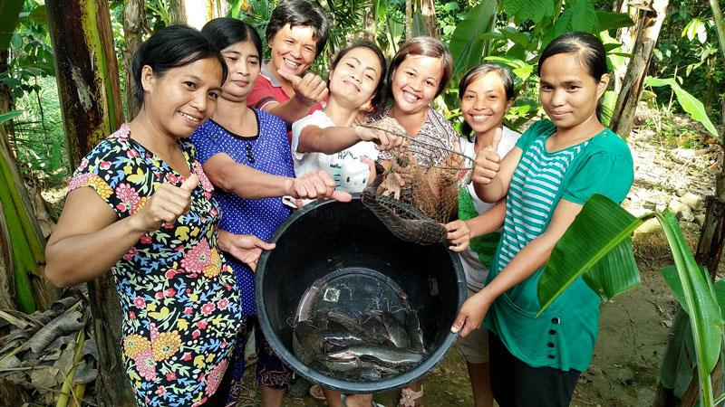 Women and bucket of catfish