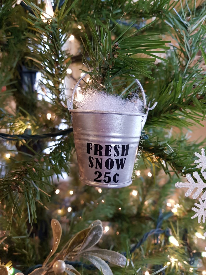 galvanized minimal hung on christmas tree and says fresh snow. has faux snow popping out of top