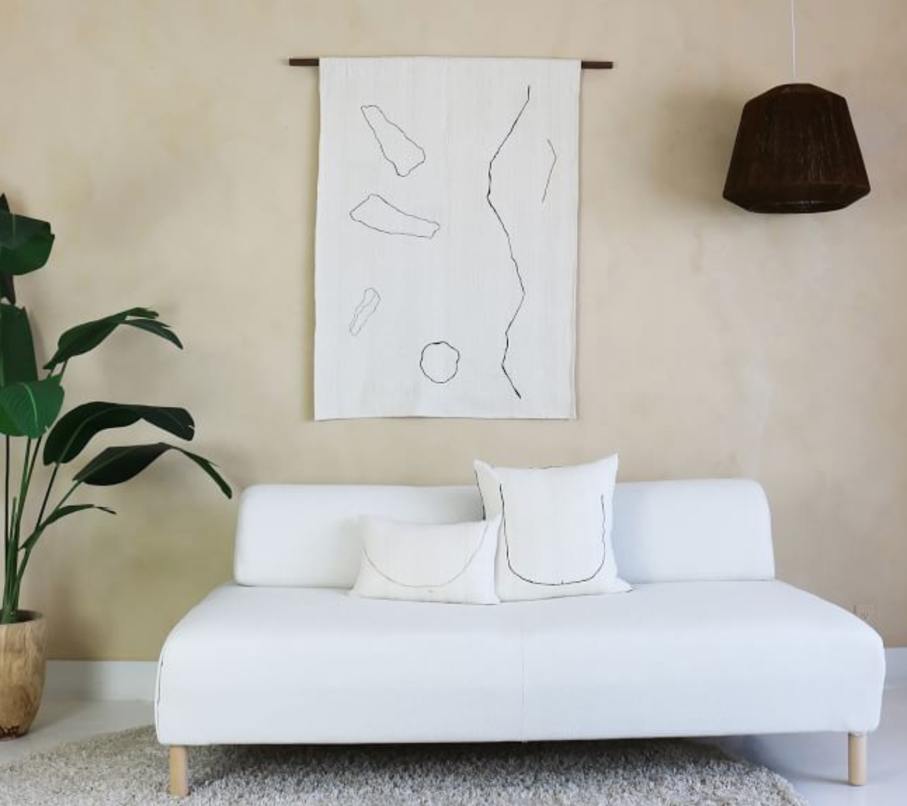 white couch with art above and houseplant next to it in apartment