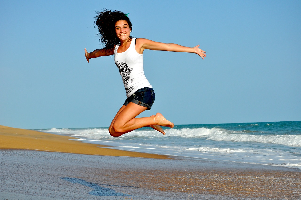 Woman in shorts and a tank top jumping next to the ocean; stay healthy traveling