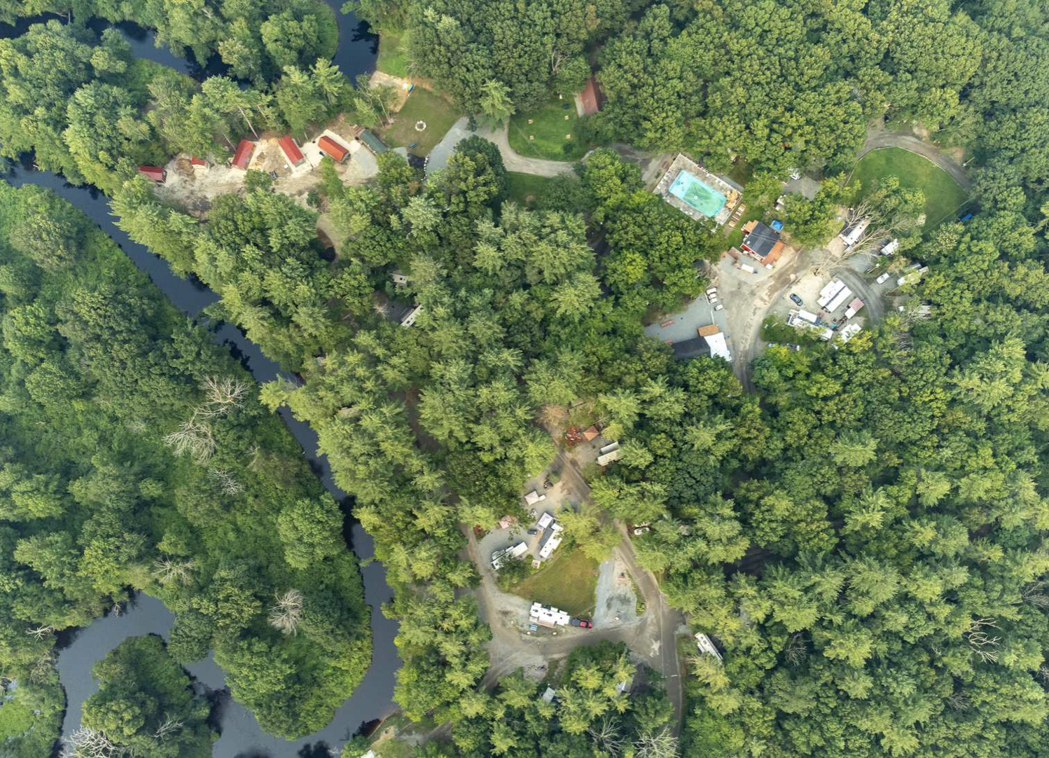 Aerial view of Exter Elms campground with trees, river, pool and cabins.