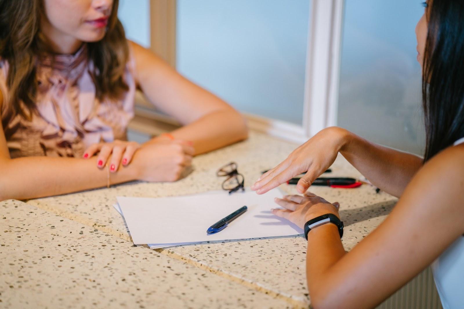 Duas mulheres conversando em uma mesa.