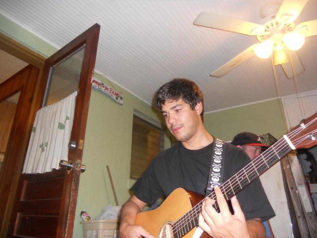 Victor playing the guitar in college in his room