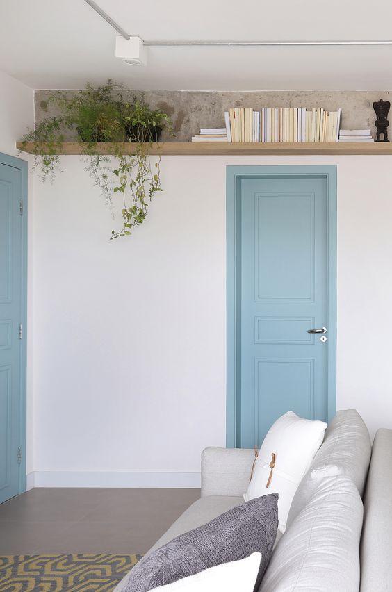 Sala pequena com decoração minimalista, paredes brancas, porta azul, sofá cinza com almofadas branca e cinza.